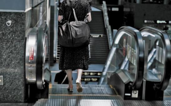 Woman descending on the escalator