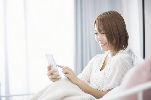 A woman who operates a smartphone with a smile