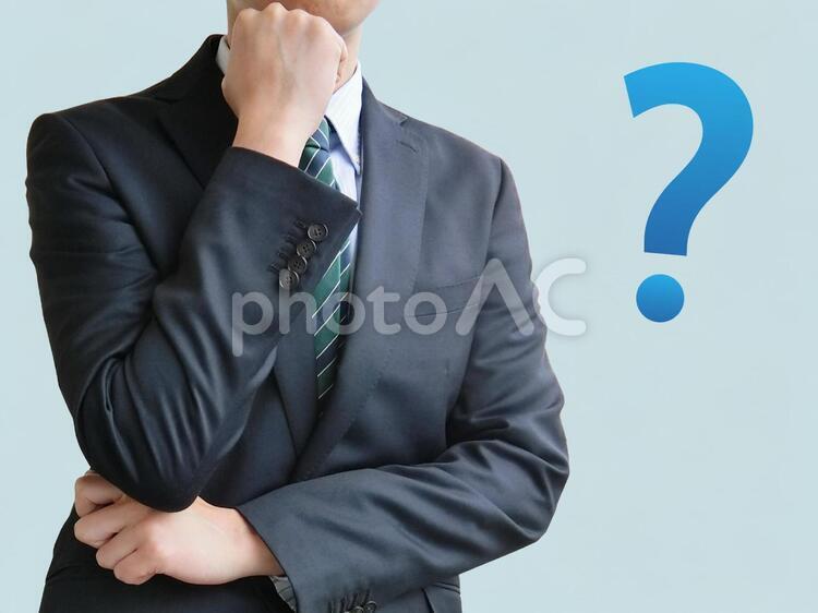 疑問に思うビジネスマン-青背景の写真