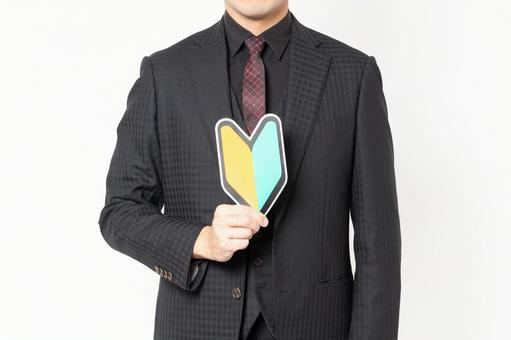 Male businessman standing in front of white background and holding a beginner mark