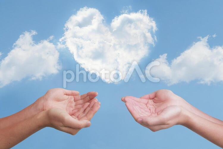 ハート型の雲と2人の救う手の写真