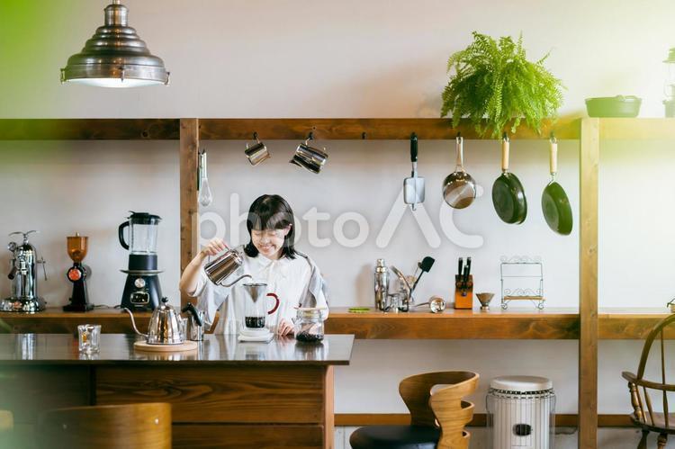 おしゃれな空間で、コーヒーを淹れる若い女性の写真