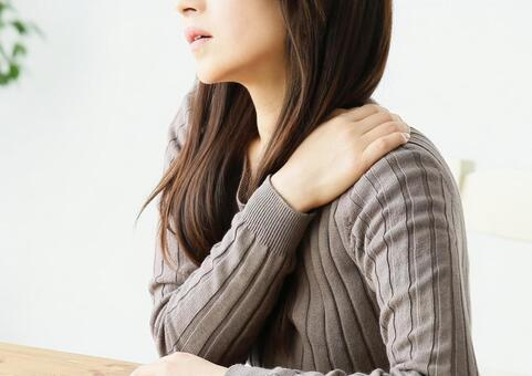 Woman suffering from stiff shoulder