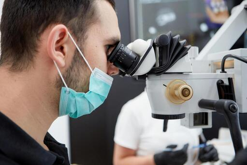Male dentist with microscope treatment 6