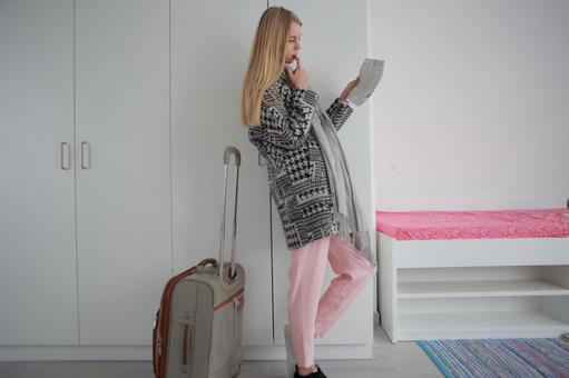 A woman in a room preparing for a room and a carry bag 4