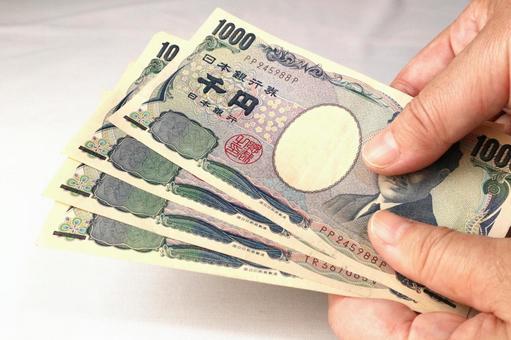 Hand holding a thousand yen bill