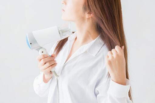 A woman wearing a hair dryer