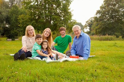 Three generation families relaxing on lawn 2
