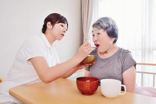 おばあちゃんにご飯を食べさせる介護士4