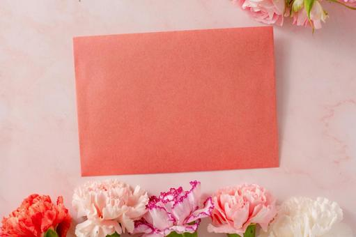 Letter on a frame of pink roses and carnations on a marble background