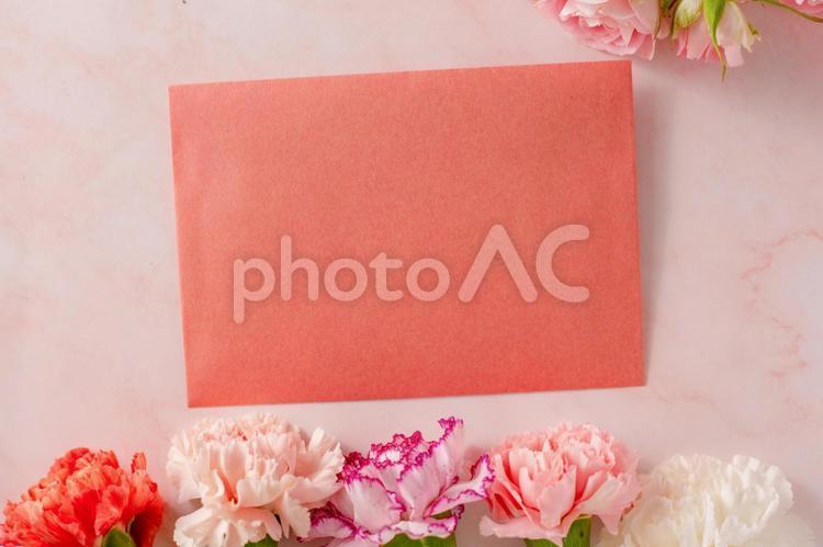 大理石の背景にピンクのバラとカーネーションのフレームに手紙の写真