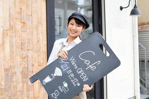 一名身穿圍裙在餐廳工作的女士在店內舉著牌子的照片