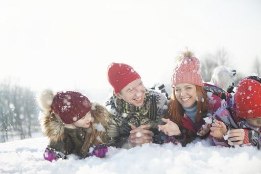 Family 2 lying down on the snow