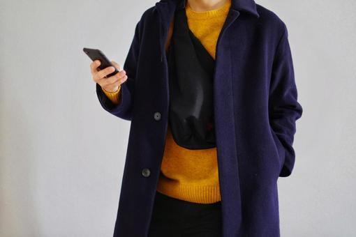 바디 가방을 걸어 스마트 폰을 만지는 코트를 입은 남자