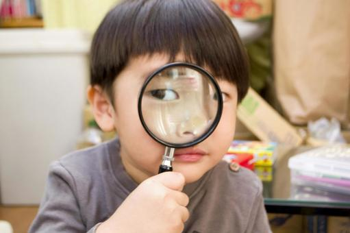 Children looking through a magnifying glass
