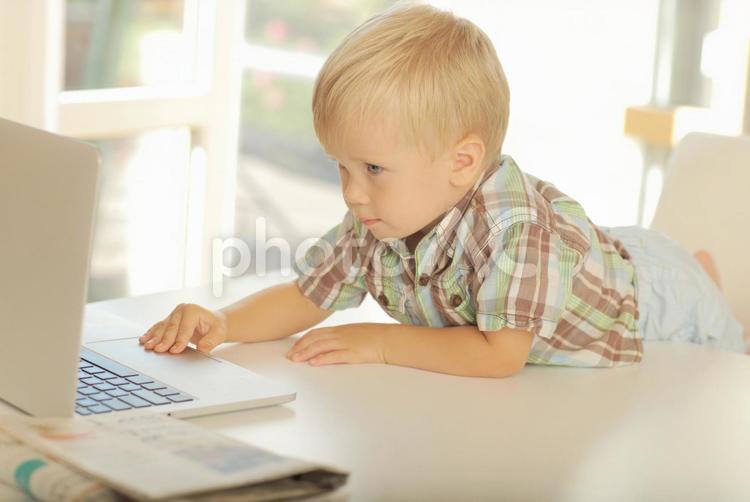 白いデスクに身を乗り出してパソコンを眺める小さな男の子2の写真
