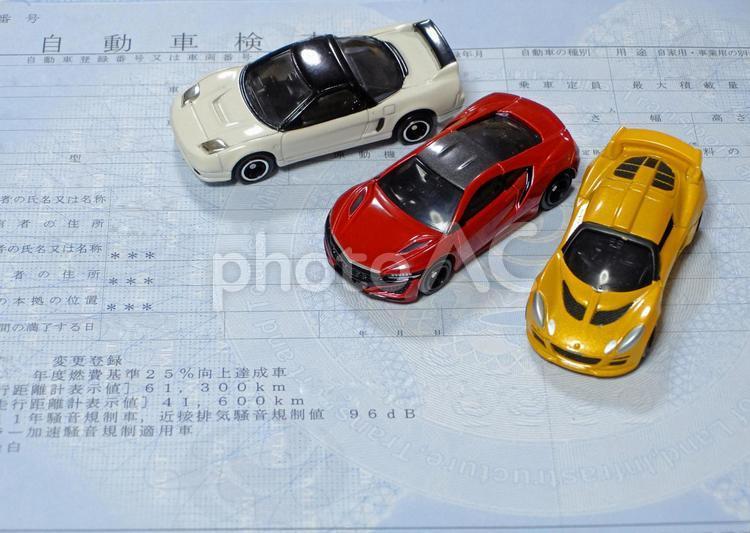 車の購入、維持をイメージした車検証とミニカーの写真