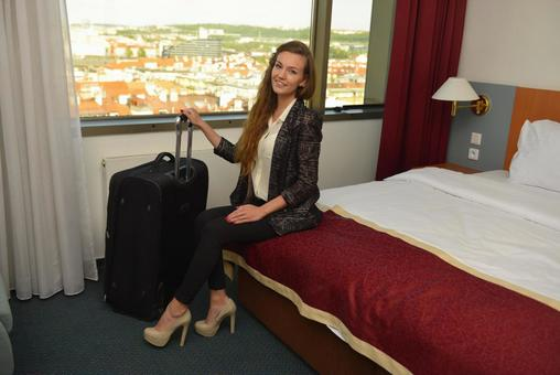 A woman sitting on a hotel bed 2