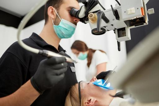 Male dentist with microscope treatment 7