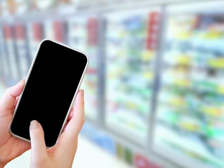 A woman touching a smartphone in front of the frozen food department