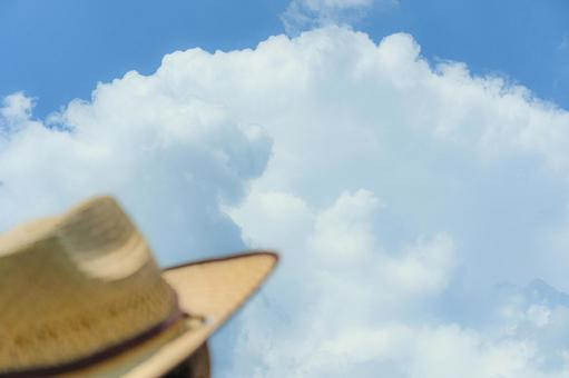 Straw hat and cumulonimbus