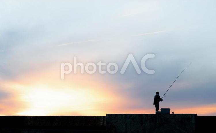 夕焼け空と釣り人のシルエットの写真
