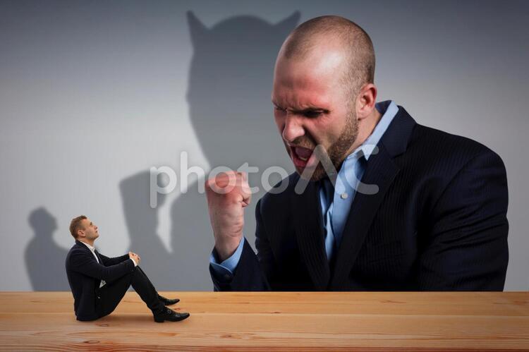 大きな人に怒られる男性の写真