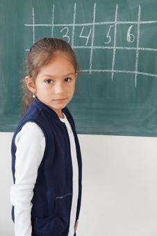 小学学生在黑板上写16