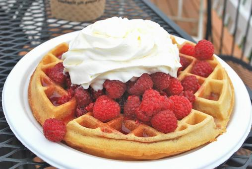 A simple waffle of freshly picked raspberries with plenty of whipped cream