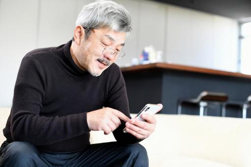 Middle-aged (senior) gray-haired man operating a smartphone