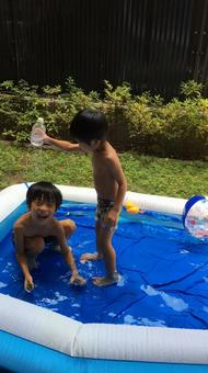 Brothers playing in a plastic pool