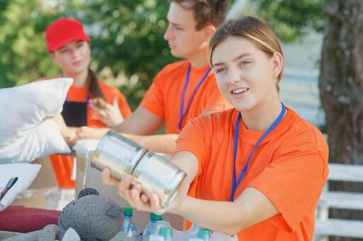 통조림을 내미는 자원 봉사자의 여성