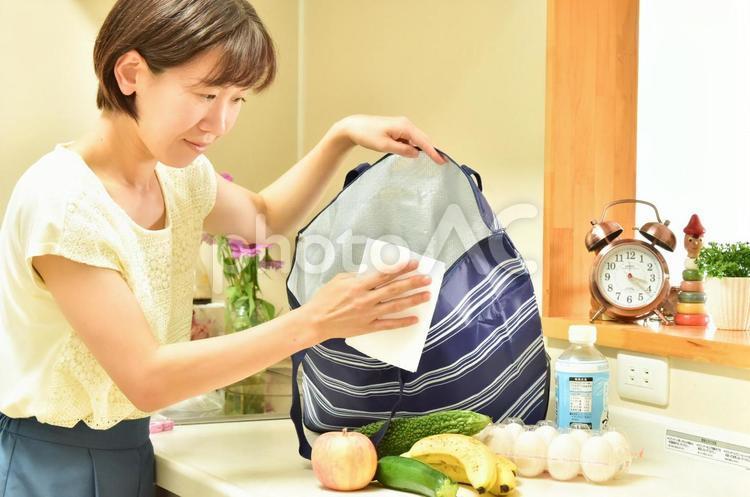 エコバッグを除菌シートで拭く女性2の写真