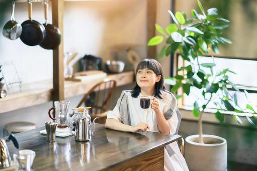 A young woman brewing and drinking coffee in a fashionable counter kitchen