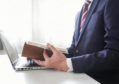 A businessman who opens a laptop and a notebook