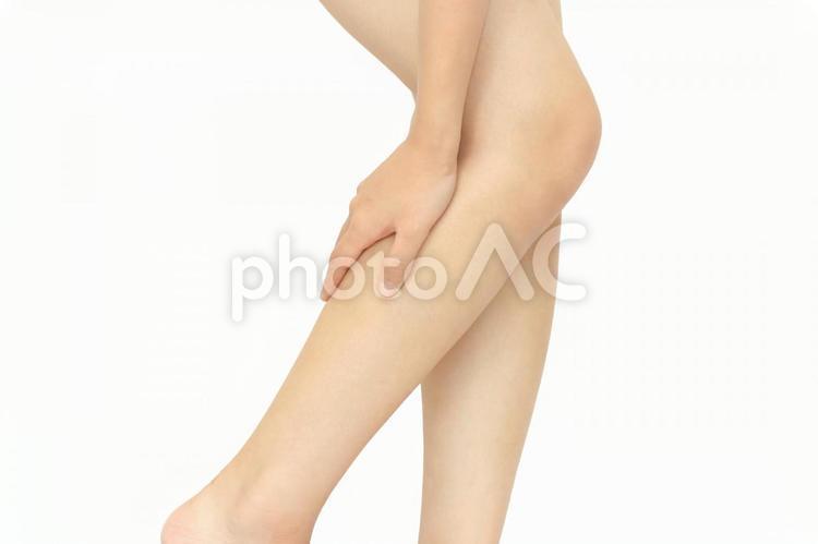 下肢に手を当てる女性1(カラー)の写真