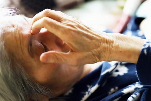 Close-up of a senior woman lying on a nursing bed and putting her hand on her face