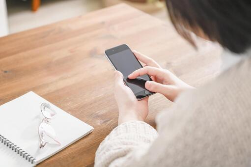 操作智能手機的女人的手