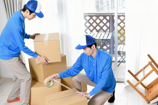 Image of multiple men in work clothes packing moving cardboard