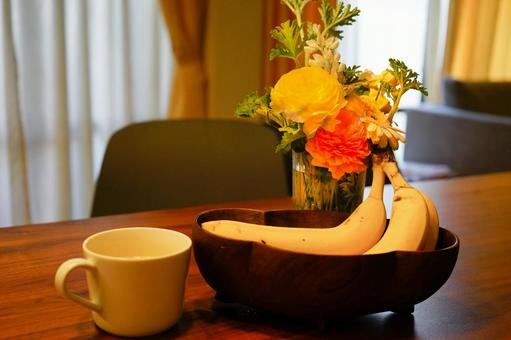 新鮮的香蕉,橙汁和桌上的鮮花