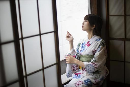 Yukata woman sitting by the window and looking out