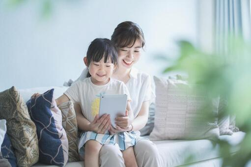 Parents and children sitting on the couch and communicating online