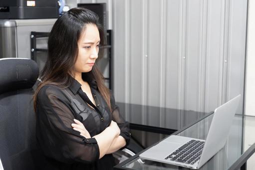 Woman looking at a computer and thinking