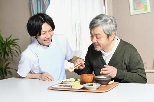 Elderly man eating and a male caregiver in an apron