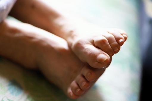 Close-up of the feet of an elderly woman lying in a nursing bed