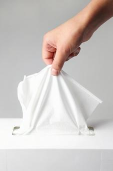 Hand grasping tissue paper