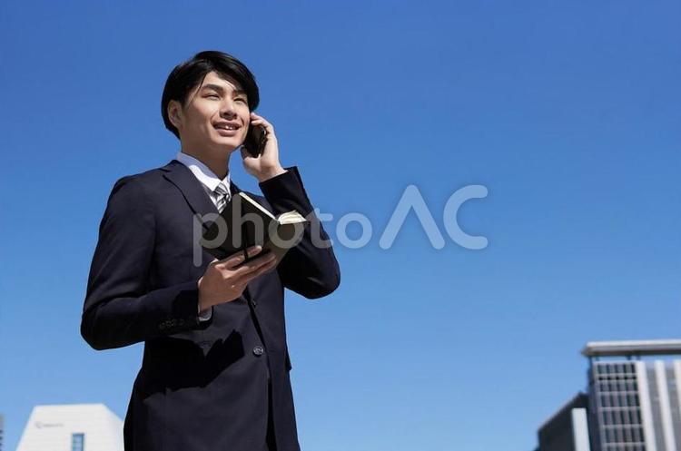 スマートフォンで通話する日本人男性ビジネスマンの写真