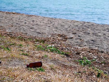 해변에 버려진 갈색 빈병