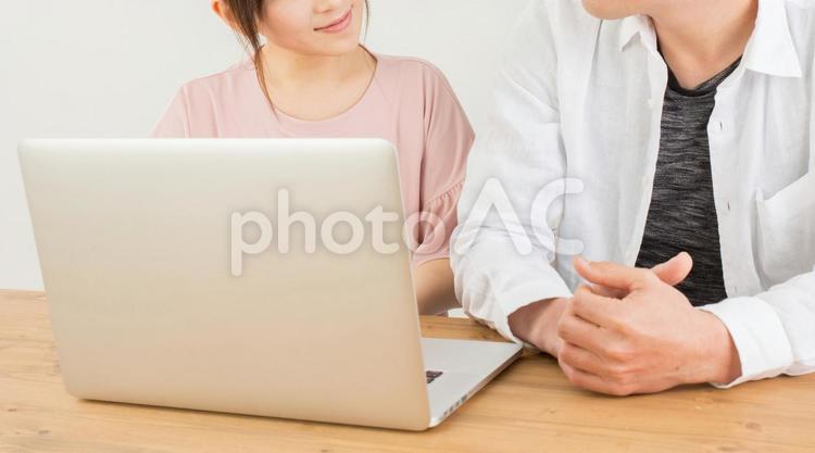 笑顔でノートパソコンを操作する男女の写真