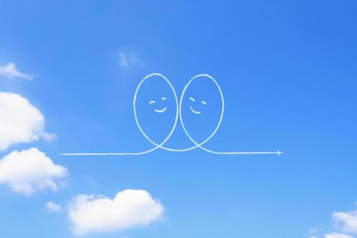 A contrail with a smiling heart drawn in the blue sky